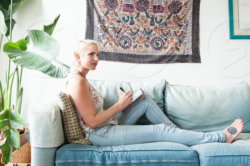 Young woman relaxes on the sofa in her colourful apartment writing in her notebook and looking deep in thought. photo