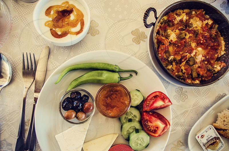 A breakfast plate including vegetables cheese yogurt with honey and menemen. photo