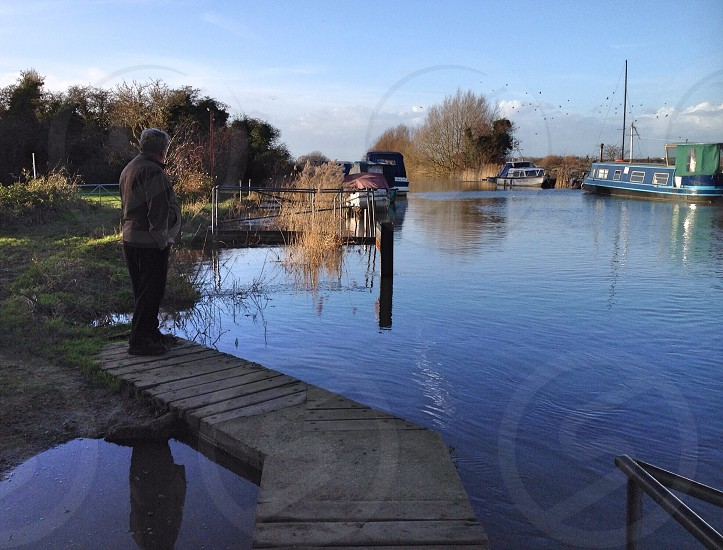 man in brown jacket standing on river side photo