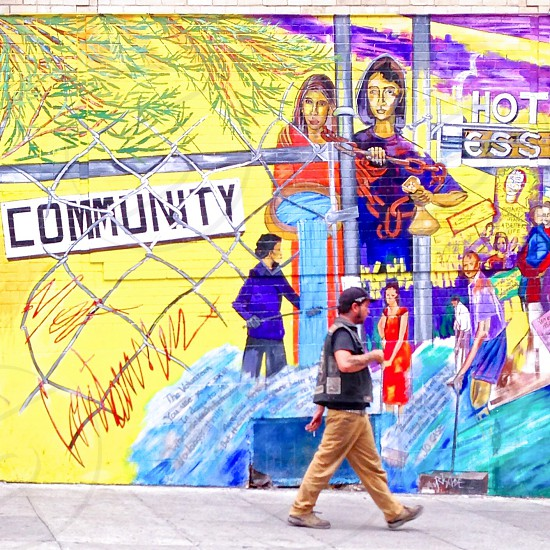 Man walking past a mural with word Community on it.  photo