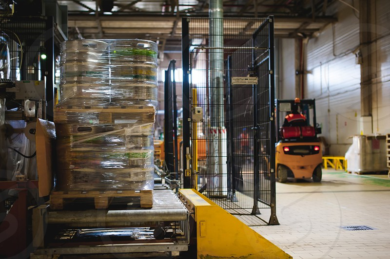 Novosibirsk Russia - APRIL 14 2017: Warehouse employee in Overalls clothes driver Reachtruck busy working logistics Moving loader pallets with beer kegs on line of factory for production of beer. photo