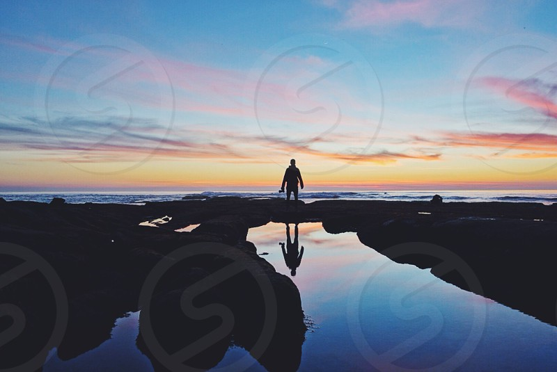 man standing on seashore with sunset view  photo