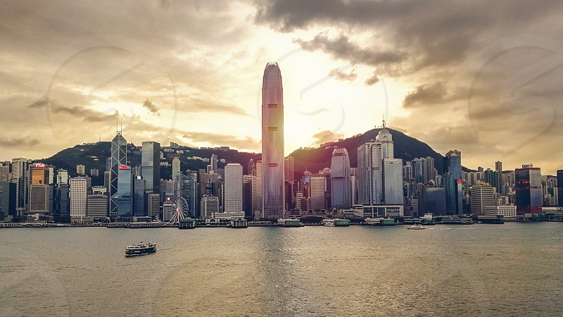 skyline of hong Kong island Victoria harbour during sunset hours with star ferry approaching tsim sha tsui jetty photo
