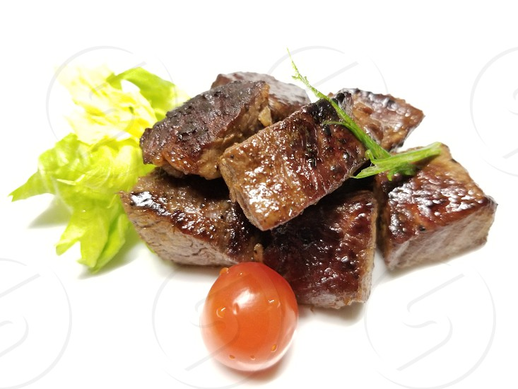 Grilled Filet Mignon cubes on a white background with lettuce tomato and scallion photo