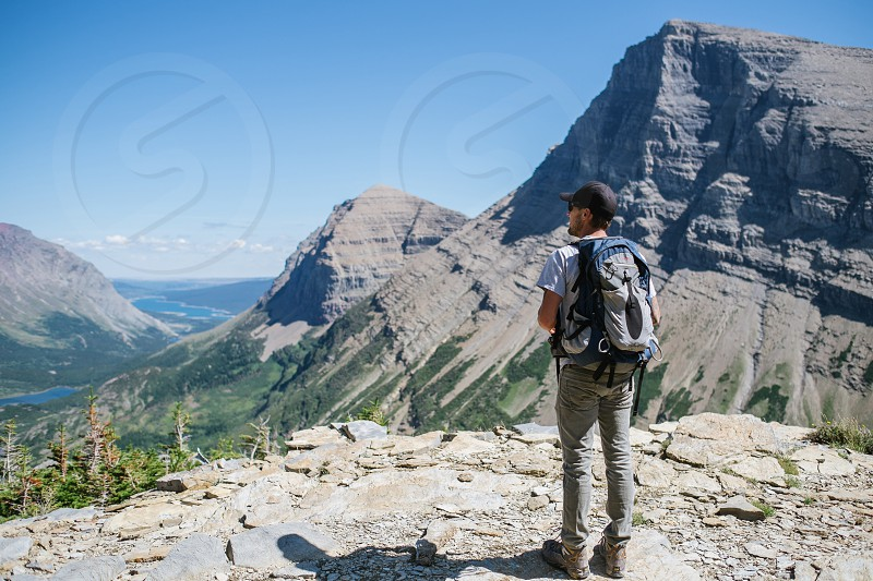 man standing in front of gray concrete mountain photo