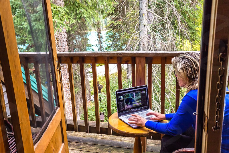 Woman using computer in remote cabin photo