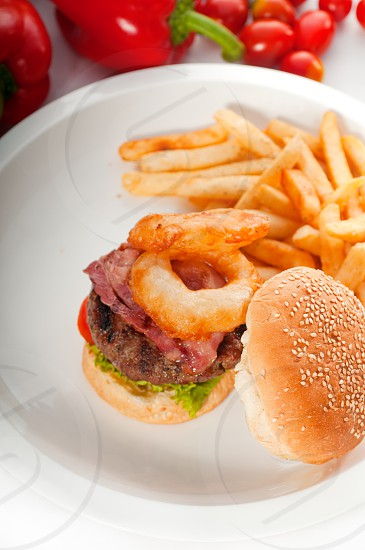 classic american hamburger sandwich with onion rings and french frieswith fresh vegetables on background MORE DELICIOUS FOOD ON PORTFOLIO photo