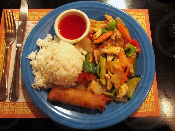 Thai red curry with spring roll white rice and sauce on blue plate photo