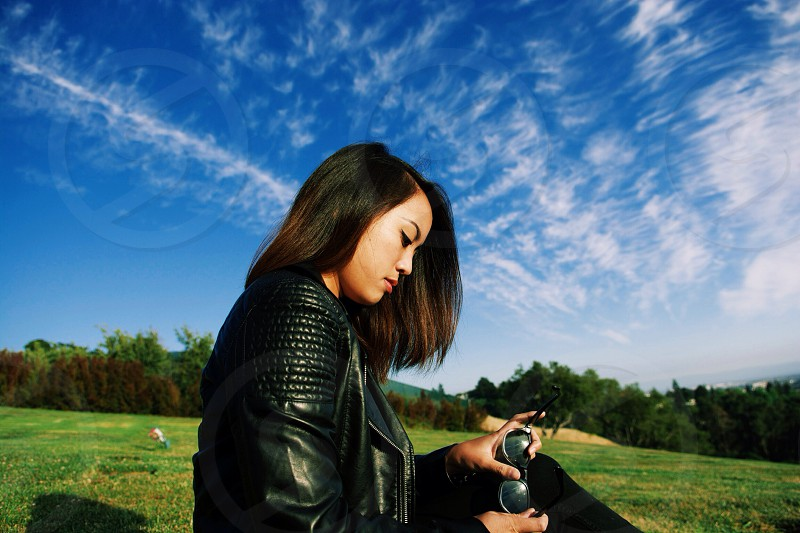 woman in black leather jacket sitting on green grass photo