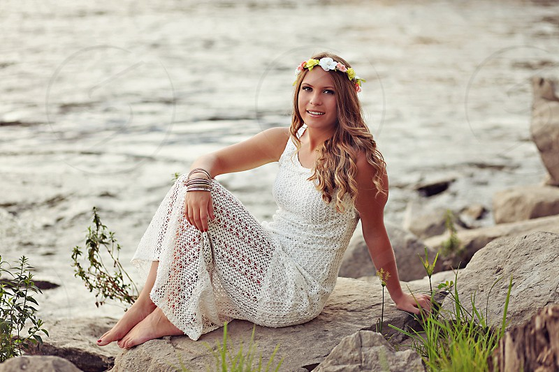 woman in white eyelet lace maxi dress sitting on a rock by the sea photo