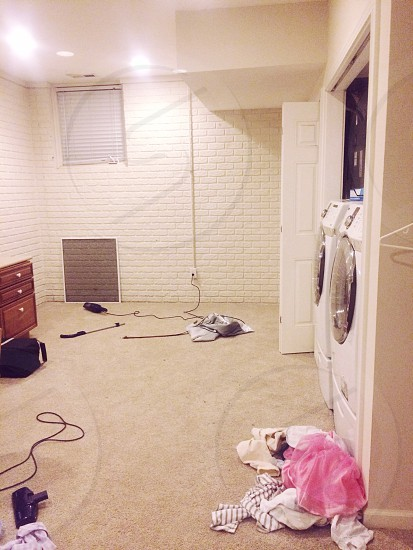 laundry room with clothing in front of machines  photo