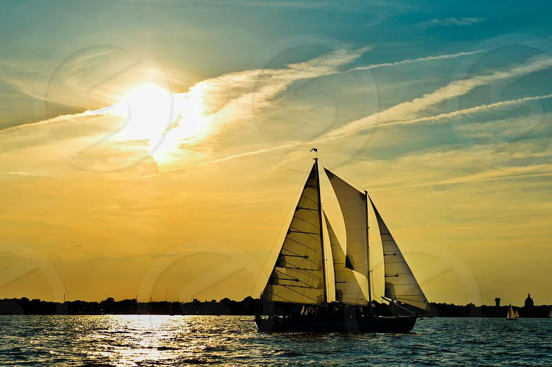 Sailboat in water against a blue and yellow sunset. photo