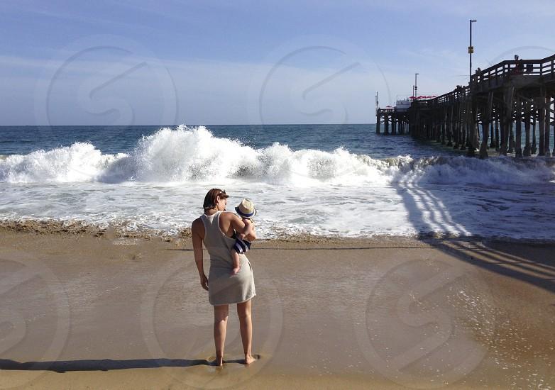 mother child watching crashing waves summer beach pier Newport California Summer family love son sun travel vacation photo