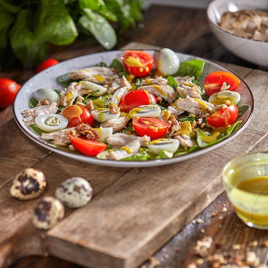 Appetizing homemade salad with fresh healthy ingredients - ripe vegetables chicken meat in a ceramic plate with olive sause on a wooden background. photo