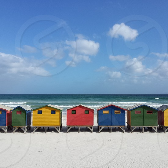 Colorful beach huts and blue sea and sky in Muizenberg Cape Town. red yellow green blue beach huts ocean sea muizenberg sky summer photo