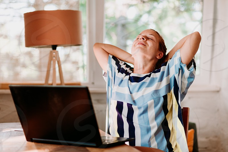 Young woman working on laptop stretching neck and arms photo