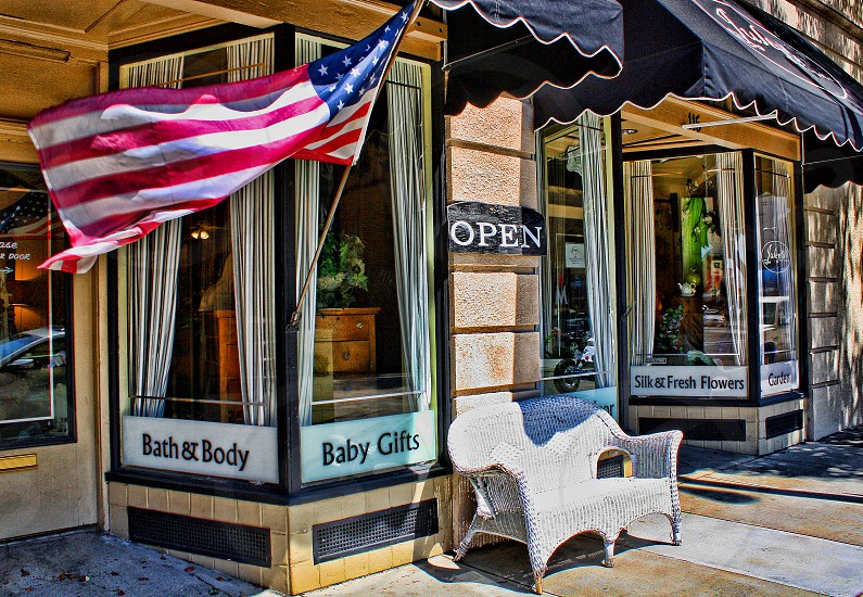 An american flag blows in the wind on a small bath and body storefront photo