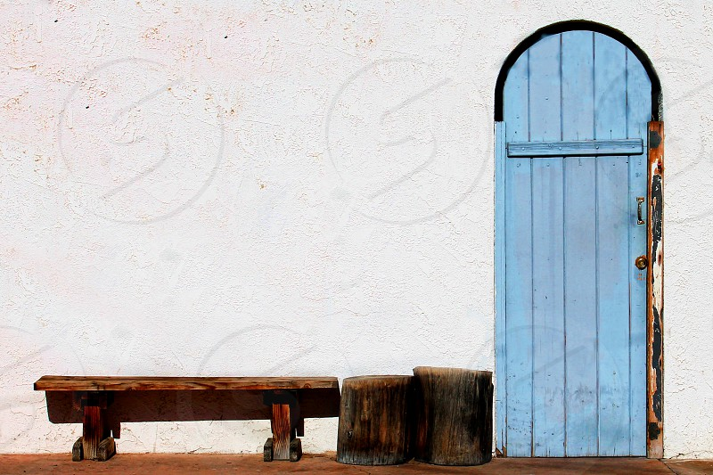 A wooden bench is outside of a white building with an old painted blue door. photo