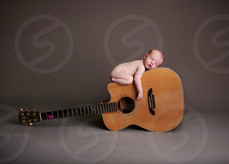 Newborn baby boy laying on top of a guitar; musical instrument. photo
