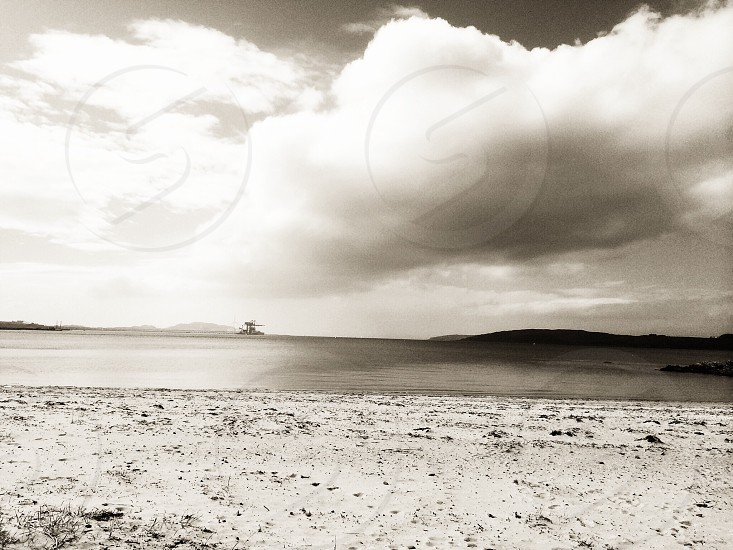 white sand beach with cumulus clouds in grayscale photograph photo