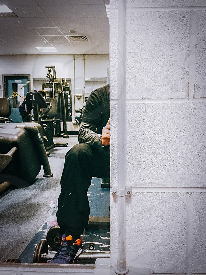 man wearing black t shirt with gray sweater inside and black sweat pants taking self portrait on mirror inside the gym photo