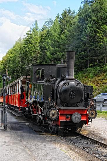 Pertisau Tirol/ AUSTRIA July 13 2013: historical steam locomotive on Achensee lake railroad in tirol town Pertisau (Austria). People waiting inside to go on a trip around the lake.  photo
