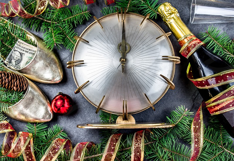 NEW YEAR CELEBRATION. Traditional put money to shoe for have money en New Year. Flat lay composition with vintage clock shoes with dollars champagne Christmas decorations. photo