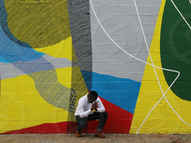 man in white dress white and black jeans seating in front of yellow green blue and red graffiti photo