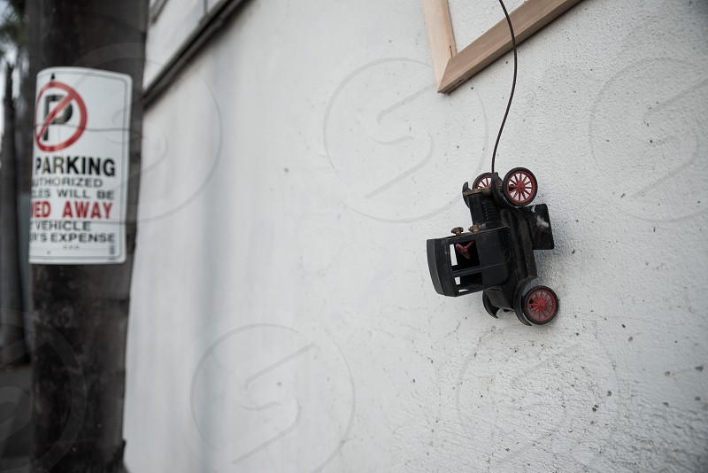 a toy car hangs auspiciously next to an ironic no parking sign in a downtown alleyway.  photo