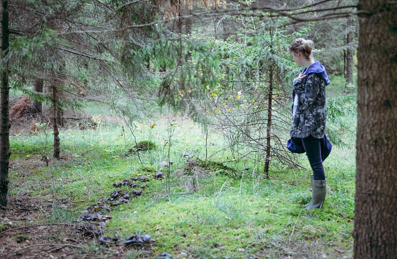 woman in grey and green camouflage hoodie on green grass by green pine trees photo