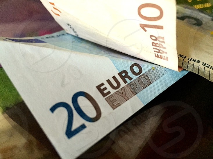 10 and 20 Euro banknotes on brown surface photo