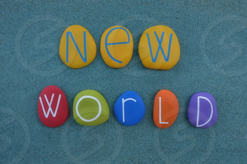 Unique slogan idea for a New World composed with carved and multicolored painted stones over green sand photo