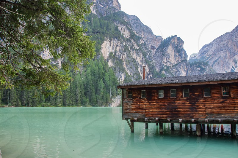 wooden cabin over the emerald water of Lake of Braies an alpin lake in Alto Adige Italy  photo