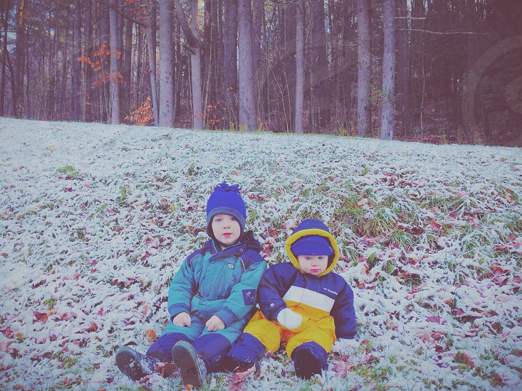 Two children brother and sister sitting in the snow photo