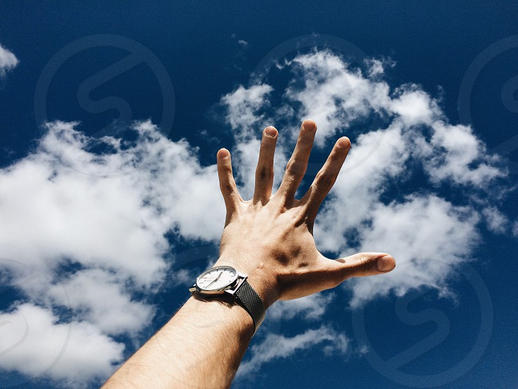 man with watch hand up to blue sky photo