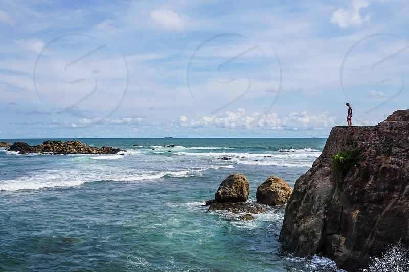 person standing on top of brown rocky cliff facing rippling body of water photo