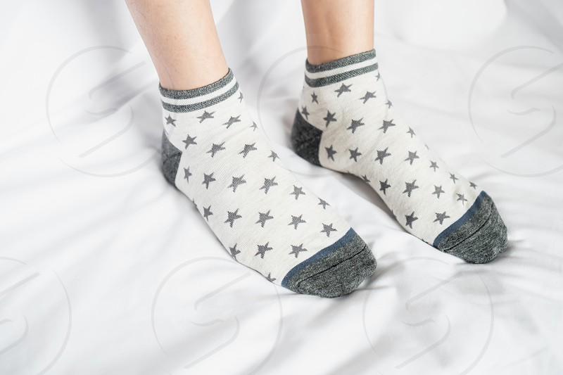 Women's legs in socks colors alternating side stand on white fabric floor. photo