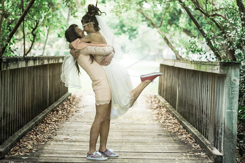 Two brides wearing veils on their wedding day embracing each other on a bridge.  photo