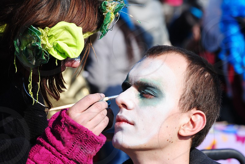 woman painting man's face photo