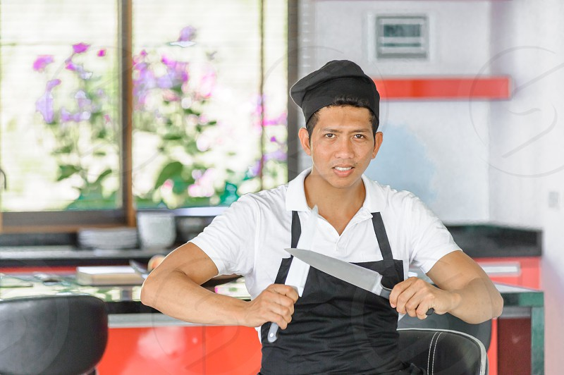 Private Thai chef in a modern style home kitchen. He sharpens knives photo