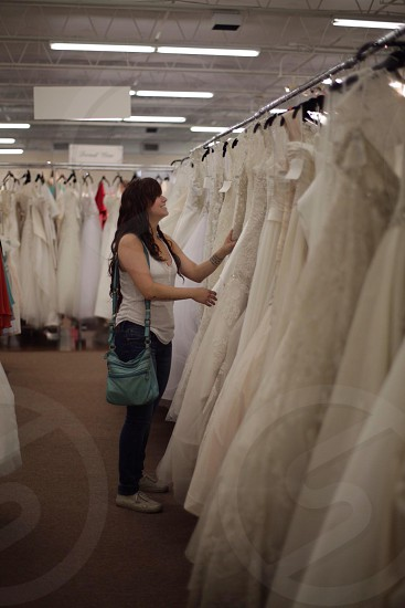 woman in white tank top with green sling bag choosing wedding gown photo