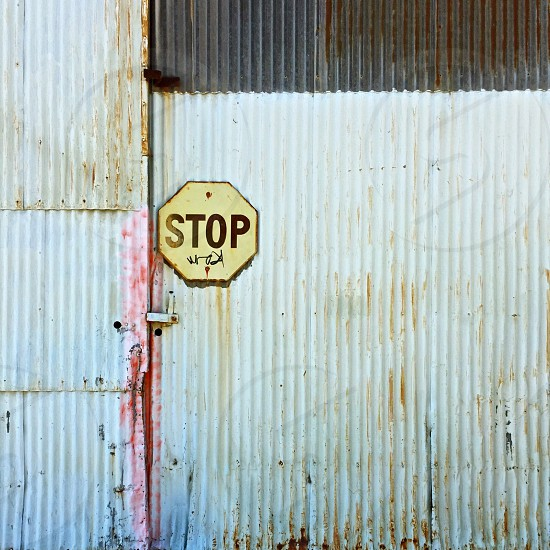 Yellow stop sign on corrugated wall.  photo