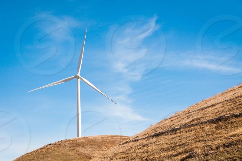 white windmill on brown mountain photo