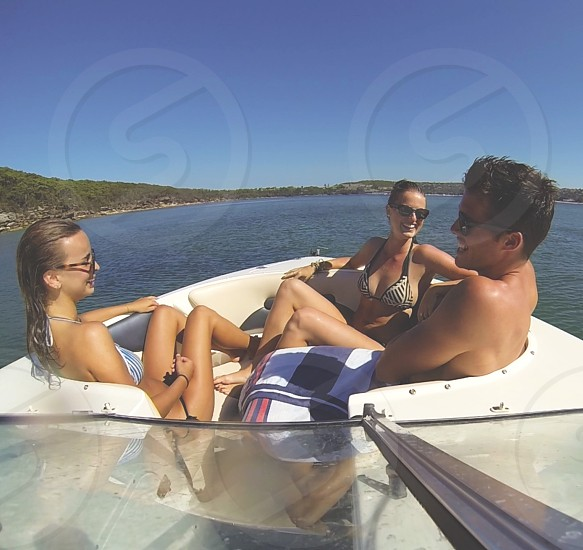two women and one man on boat photo