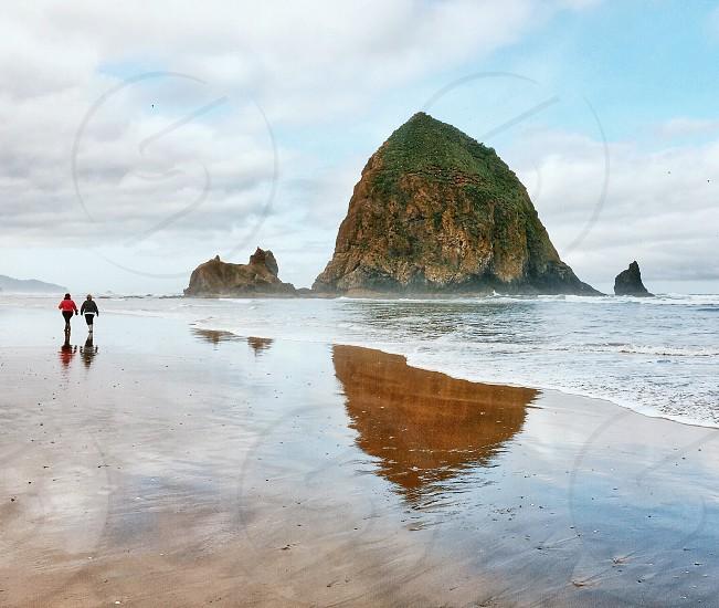 people walking on the beach next ot large rock photo