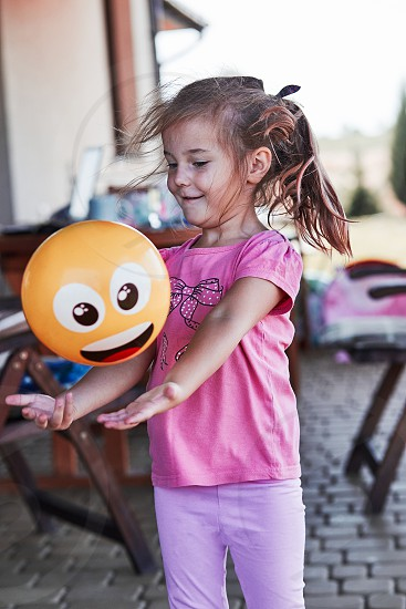 Little adorable girl playing with ball in a home playground in a backyard. Happy smiling kid having fun on a play house on summer day. Real people authentic situations photo