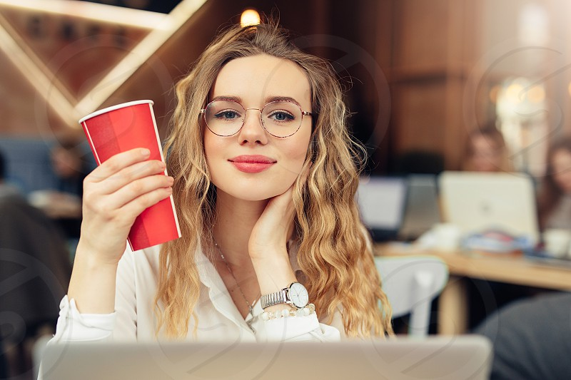 Woman Wear Glasses Drink Her Hot Coffee While Work In Cafe On Her Laptop. Portrait Of Stylish Smiling Woman In Winter Clothes Drinking Hot Coffee And Work At Laptop. Female Winter Style. - Image photo