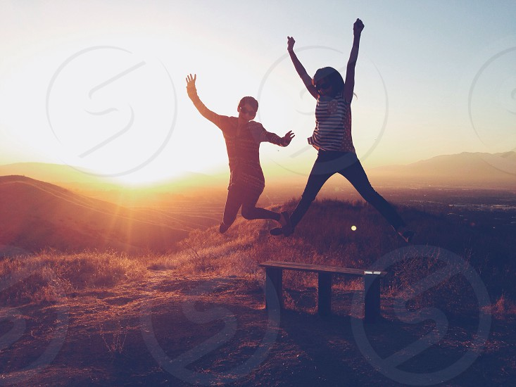 two person jumping photography photo
