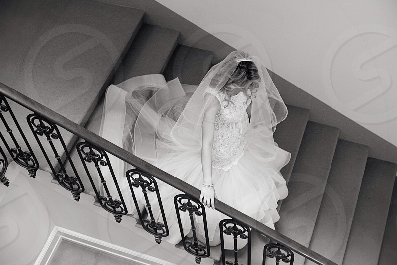bride in white walking down a staircase grayscale photo photo