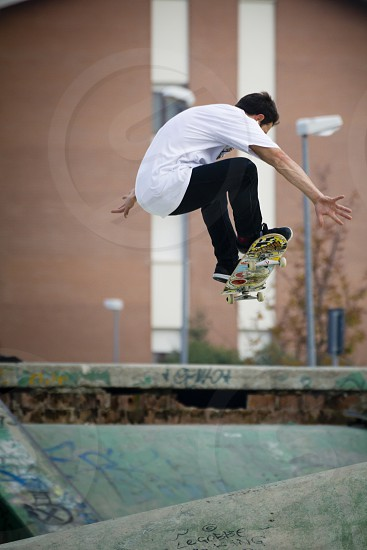 A young boy jumping with skateboard.  Imperia IM Liguria Italy - October 26 2016: A young boy jumping on the skateboard in a skatepark during a sports competition of the city of Imperia. photo